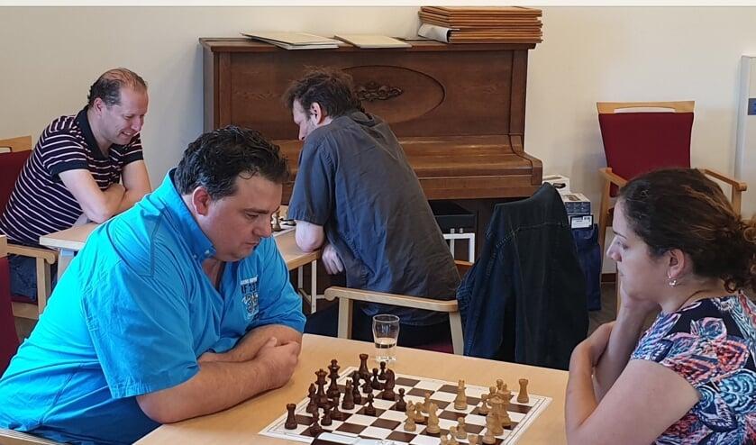 Warner de Weerd (links) in actie tegen de vrouwelijke grootmeester Bianca Muhren-De Jong. Die pot won hij nog waardoor hij na vier ronden de maximale score had. Op de achtergrond links internationaal meester Jan-Willem de Jong en rechts Marc Helder.