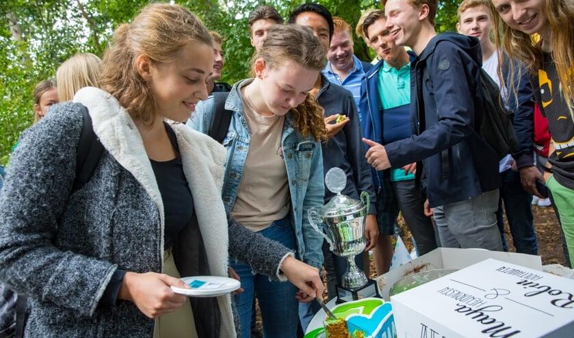 De 2 winnaars Robin Holthuizen en Maya Hendriksen snijden de taart aan.