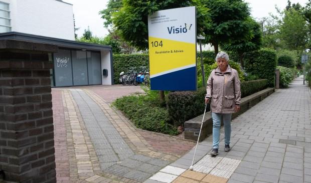 Blinde vrouw loopt met taststok over geleidelijn.