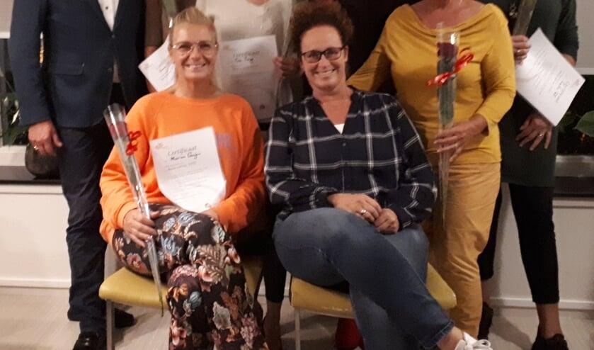 Coördinator Marieke Zwart (zittend in het midden) met een aantal vrijwilligers.