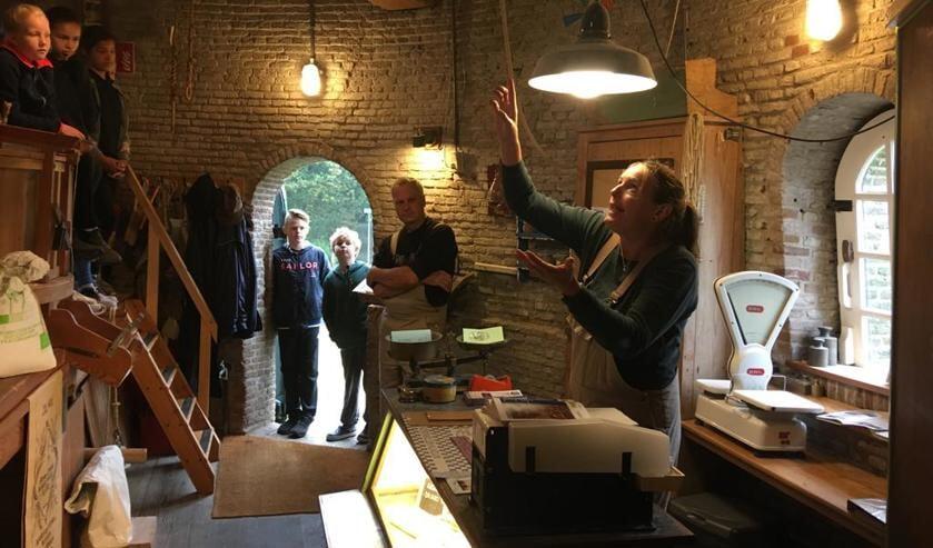 Vrijwillig molenaar Tessa Krop met leerlingen groep 7 op bezoek in de molen, hier op 'de maalvloer
