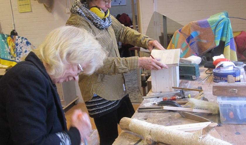 Ellie en Roos bezig met houtbewerken.