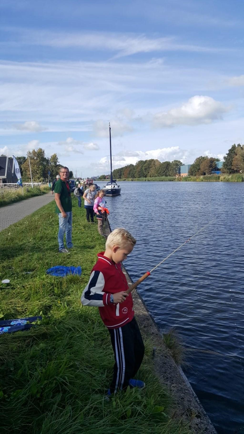 Groepje kinderen vangen vissen tijdens cursus.  © rodi
