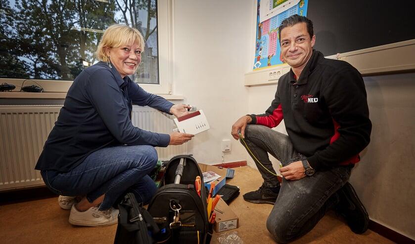 Samen met een monteur van Trined activeert directeur Mariska Buizer (l) van OBS Prinses Beatrix de eerste glasvezelaansluiting in Kwadijk.