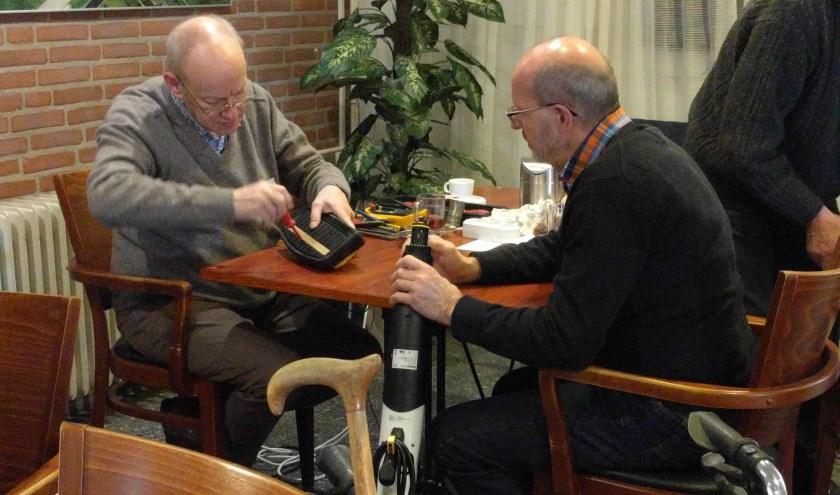 Een vrijwillige reparateur is bezig met een kapot apparaat, de eigenaar kijkt toe.