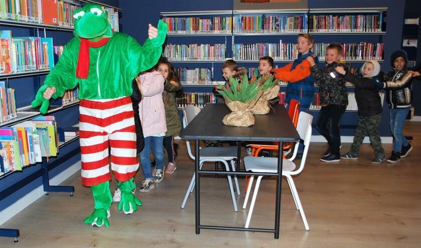 Tijdensopening opendehet boekenfiguurtje Kikker de bieb samen met kinderen van de drie basisscholen uit de Schooten.