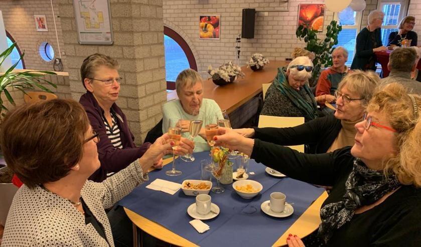 Vrijwilligers proosten met elkaar op het nieuwe jaar.
