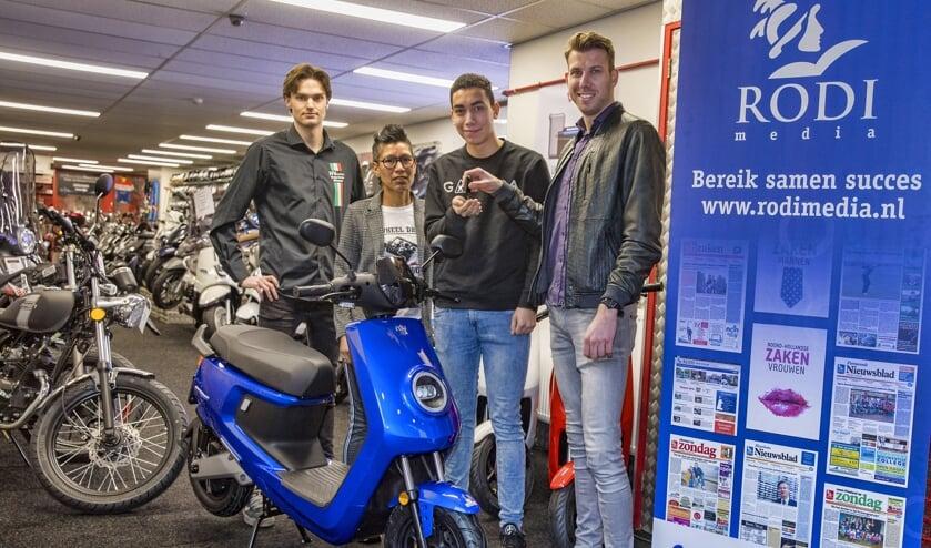 Christian van Goethem van Rodi Media overhandigt de sleutels aan de scooter-winnaar Milan Gennissen.