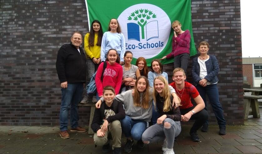 Een deel van eco-team The Greenies poseert trots voor de Groen Vlag met hun begeleidende docenten Jacob Jeltes en Marieke Brehm)