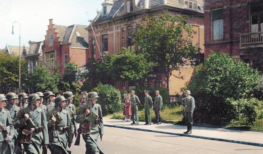 Soldaten marcheren in 1942 over de Alkmaarse Kennemerstraatweg op deze ingekleurde foto.