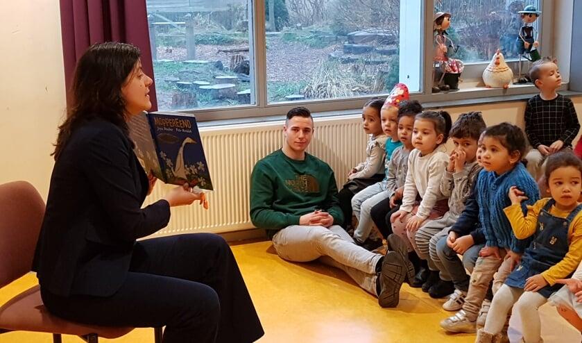 De wethouder leest voor, de kinderen luisteren.