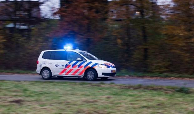 Politieauto met zwaailicht aan.
