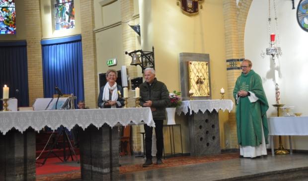Nel van Schagen poseert trots met haar onderscheiding, naast haar staat haar echtgenoot. Pastoor Tilma kijkt toe.