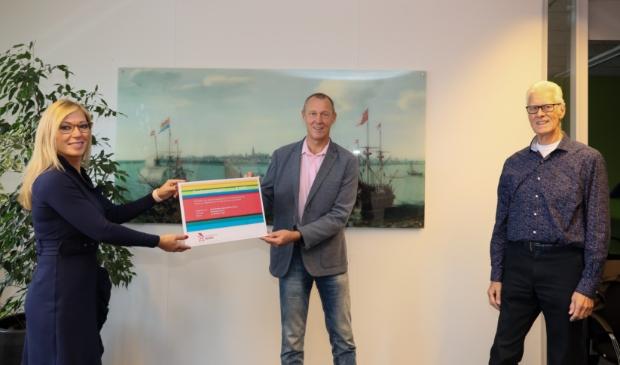 <p>Wethouder Kholoud al Mobayed reikt een Eenhoornzegel uit aan voorzitter Henk Snoeijer en penningmeester Jan van den Bos. </p>