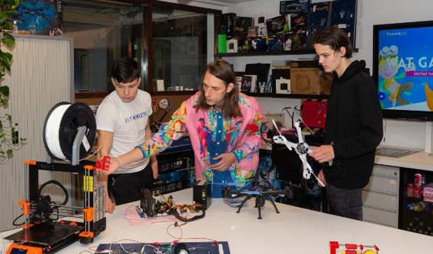 <p>Toine Rohner (midden) geeft uitleg over drones aan Julian (links) en Mex.&nbsp;&nbsp;</p>