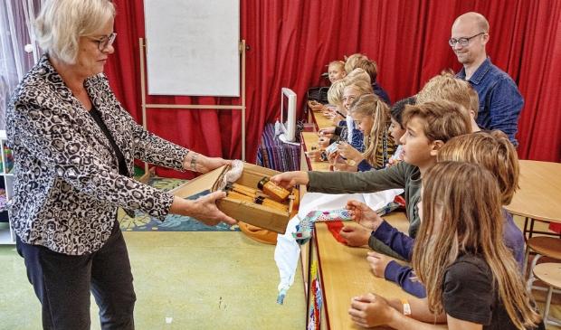 Elly Beens reikt mondharmonica's uit op de Willbrordusschool.
