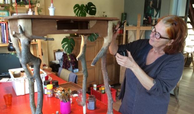 Kien Hertoghs werkt aan een kastje met pootjes van boomtakken.