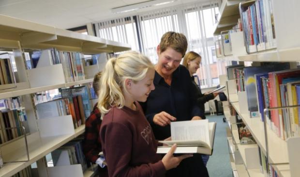 <p>Linda Visser adviseert een leerling in de mediatheek op het Martinuscollege.</p>
