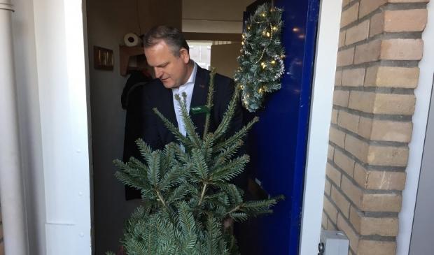 <p>Wethouder Gerard Slegers (openbare Ruimte) brengt een kerstboom langs bij een van de bewoners van Pennemes </p>