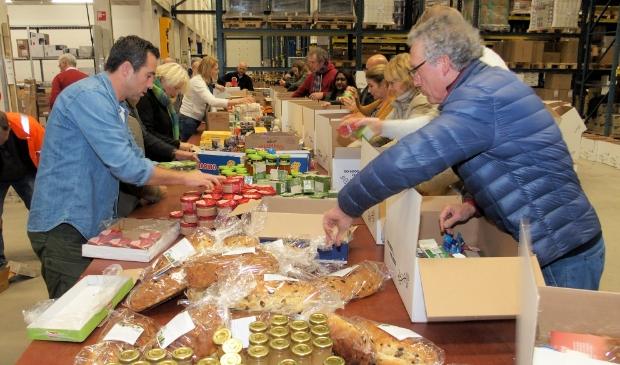 <p>Leden van de rotaryclubs helpen bij het inpakken van de pakketten.</p>
