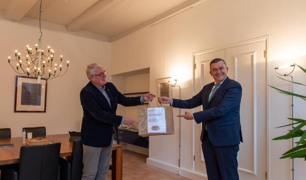 <p>Harry van de Kuijt, voorzitter Rotaryclub Alkmaar overhandigt het eerste boerenkoolmaaltijdpakket aan Emile Roemer, burgemeester van Alkmaar.&nbsp;</p>