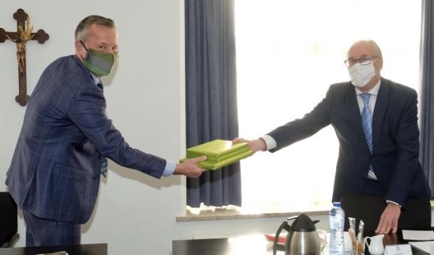 <p>Burgemeester Romeyn geeft boeken over Heiloo mee aan de Commissaris van de Koning.</p>