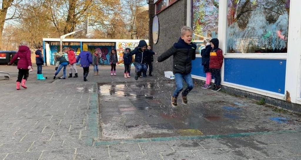 Op het schoolplein van De Kustlijn doen kinderen mee aan het NK Plassen Stampen. (Foto: Yvette van der Does) © rodi