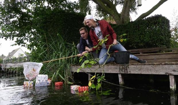 <p>Vin en Frank vissen de pakjes uit het water.</p>