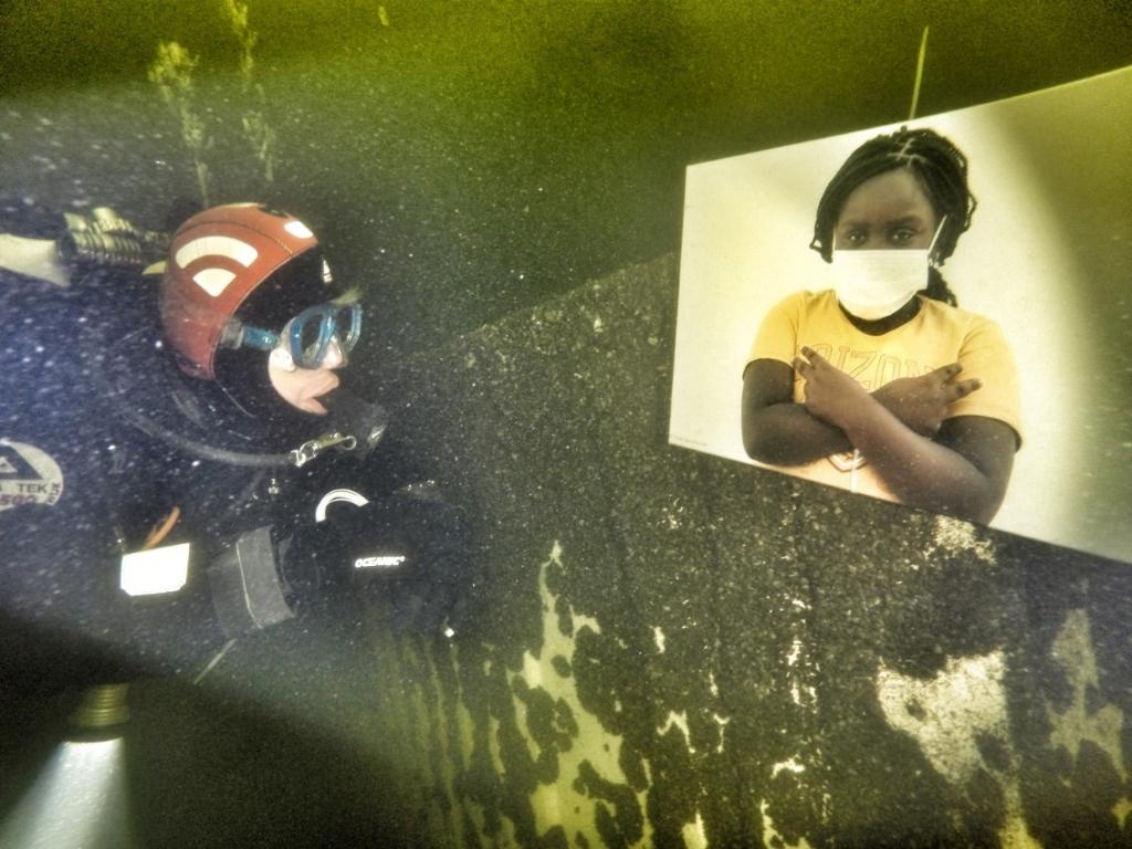 <p>Duiker bekijkt onder water de foto van meisje met mondkapje</p> (Foto: annelies versteege) © rodi