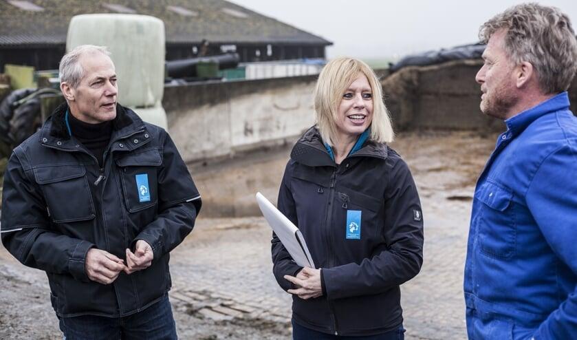 Toezichthouders Mariëlle Schagen en Bart Sprenkeling in gesprek met veehouder Jan Out (r).