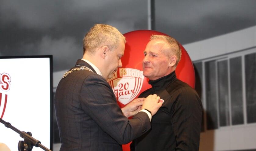 Dennis gebbink krijgt zijn onderscheiding opgespeld door de waarnemend burgemeester van Landsmeer, Dennis Straat.