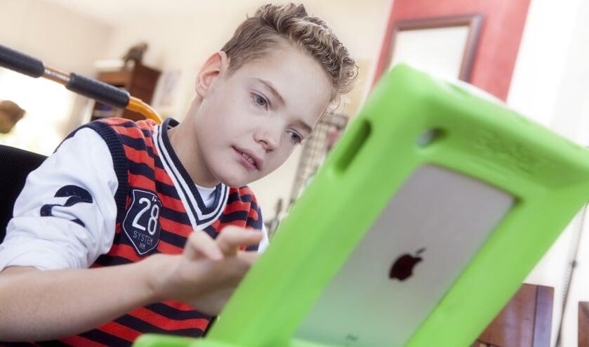 Slechtziende jongen kijkt op iPad.