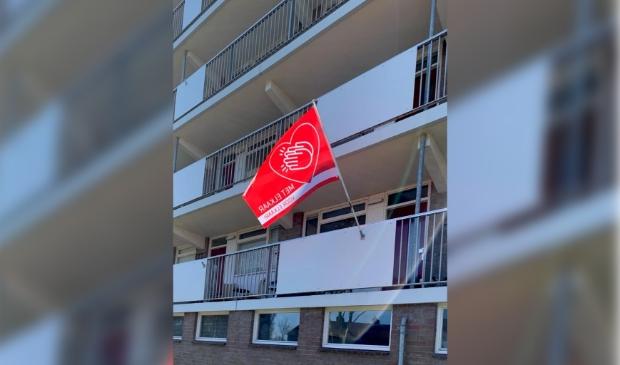 Vlag 'Met elkaar en voor elkaar' hangt aan de galerij van een flat in Krommenie.