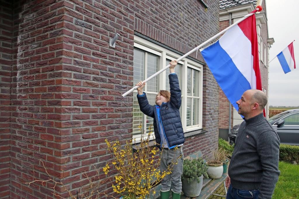 Stefan en zijn zoontje hingen vrijdagochtend de vlag uit als steunbetuiging. (Foto: Theo Annes) © rodi