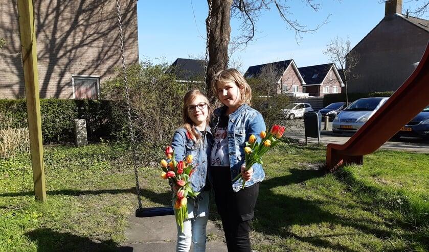 De zussen Charisa (r) en Charill hebben tulpen rondgebracht in hun eigen buurt in Zwaag.