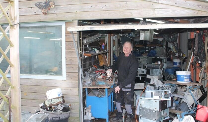Jelle aan het werk in zijn garage waar hij alle apparaten uit elkaar haalt en oud ijzer verzamelt.