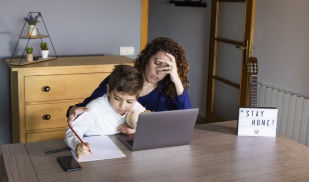 Moeder probeert thuis te werken in quarantainetijd.