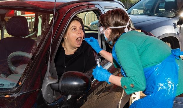 Alle zorgmedewerkers worden vanuit de auto getest door GGD-medewerkers in beschermende kleding.