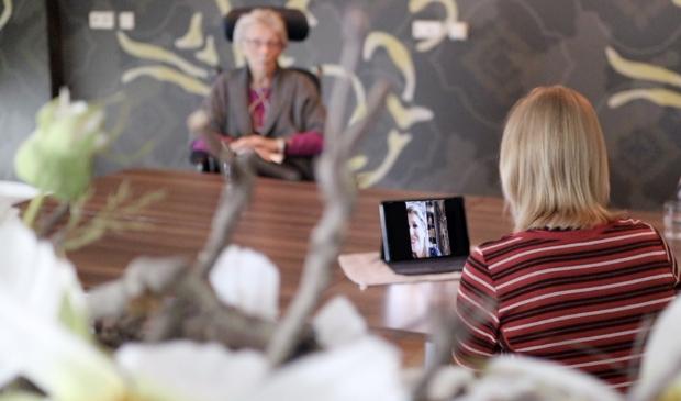 Locatiemanager Petra Oudt heet Koningin Máxima via het scherm welkom in locatie Nicolaas. Op de achtergrond mevrouw Vrieler-de Vries.