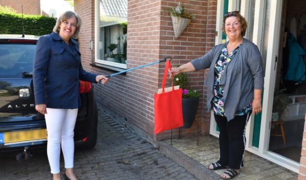Mevrouw Kenter-de Lange kreeg als eerste het bouwpakket met knutselmateriaal van Wethouder Yvonne Roos-Bakker.