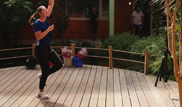 Tessa Scholte doet de oefeningen tijdens de balkongym voor aan de bewoners van het Heiligharn in Den Helder. (Foto Team Sportservice)