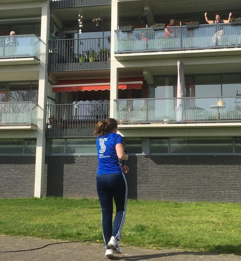 Tessa Scholte doet de oefeningen tijdens de balkongym voor aan de bewoners van het Heiligharn in Den Helder. (Foto Team Sportservice) (Foto: Team Sportservice) © rodi
