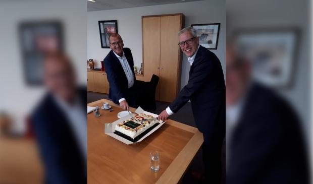 Het bezegelen van de samenwerking gebeurt door een taart aan te snijden.