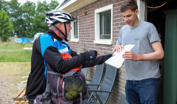 Bob ontvangt van docent Hans Visser zijn cijferlijst en een geslaagd vlag.