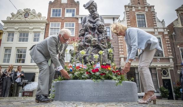 Burgemeester Piet Bruinooge en zijn echtgenote leggen een bloemstuk bij het beeld van Truus.