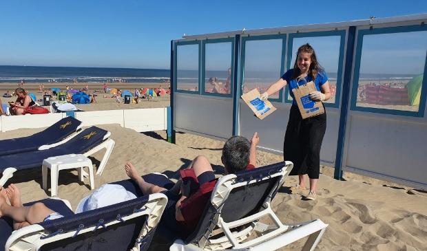 <p>Vrijwilliger van Stichting De Noordzee deelt zakjes uit aan badgasten.</p>
