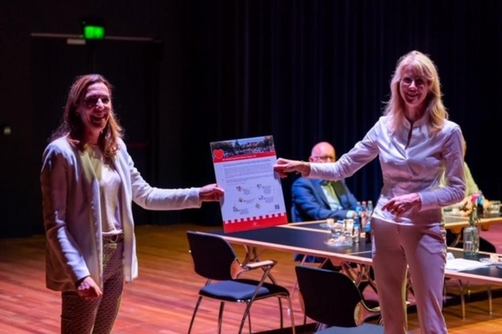 Mona Keijzer neemt eerste exemplaar flyer Stimuleringsfonds Alkmaar in ontvangs uit handen van Marie-José van den Kommer. (Foto: aangeleverd) © rodi