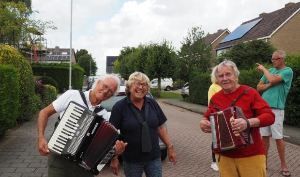 Muzikanten spelen troostmuziek in de Startingerstraat, met tussen hen in Joke de Wit.