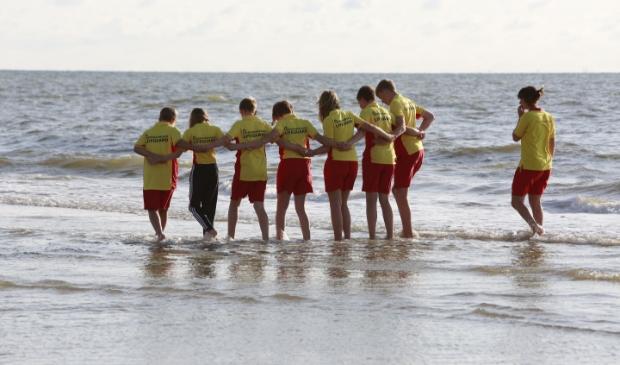 <p>Jeugd van de reddingsbrigade langs de vloedlijn in training voor reddingsacties.</p>