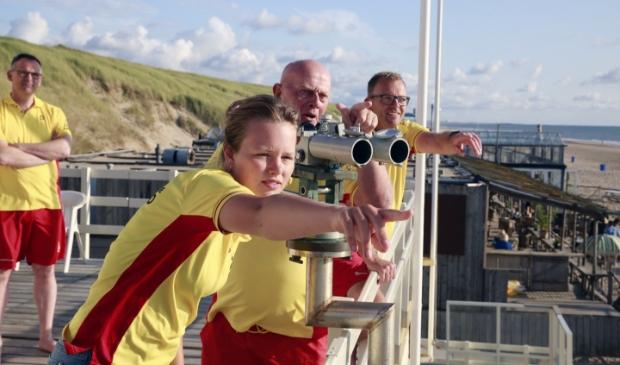 <p>Commandant Harrie Hamakers (achter de verrekijker) en de andere lifeguards van Reddingsbrigade Castricum op hun post. Ze wijzen &nbsp;naar de muien in zee.</p>